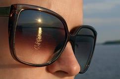 Den unga kvinnan i solglasögon ser solen på stranden royaltyfri fotografi