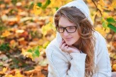 Den unga kvinnan i solglasögon som går i höst, parkerar fotografering för bildbyråer
