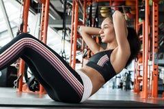 Den unga kvinnan i sportig livsstil för idrottshall på matt görande buk- knastrandesidosikt utandas arkivbilder