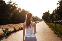 Den unga kvinnan i sportswear som går på vägen arkivfoto