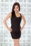 Den unga kvinnan i svart klänning ler lite med förtroende. Arkivbild