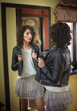 Den unga kvinnan i svart läderomslag och den gråa korta ballerinakjolen kringgår att se in i en stor spegel Härligt lockigt poser Royaltyfri Fotografi