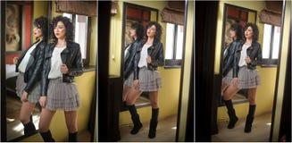 Den unga kvinnan i svart läderomslag och den gråa korta ballerinakjolen kringgår att se in i en stor spegel Härligt lockigt poser Royaltyfria Bilder