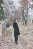 Den unga kvinnan i svart lag går på den utomhus- banan parkerar in vinter för blick tillbaka arkivfoton