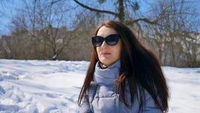 Den unga kvinnan i svart solglasögon och rakt hår som tycker om vara det fria i, parkerar i morgonen under soligt men arkivfilmer