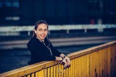 Den unga kvinnan i svarta sportar utrustar att vila, når han har kört, på natten fotografering för bildbyråer