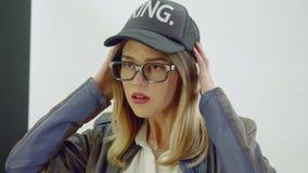 Den unga kvinnan i tillbaka omslag, lock och exponeringsglas poserar under fotoperiod lager videofilmer