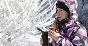 Den unga kvinnan i varmt omslag värme sig med varmt kaffe i vinter parkerar lager videofilmer