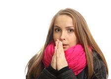 Den unga kvinnan i vinter försöker att värma henne upp händer arkivfoton