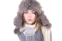 Den unga kvinnan i vinterkläder som blåser något från henne, gömma i handflatan I Royaltyfria Foton