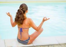 Den unga kvinnan i yoga poserar att sitta nära pöl Royaltyfria Bilder