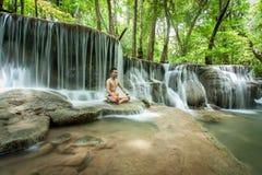 Den unga kvinnan i yoga poserar att sitta nära vattenfallet, Huai Mae Khamin Fotografering för Bildbyråer