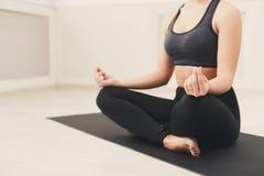 Den unga kvinnan i yogagrupp, kopplar av meditation poserar arkivbild