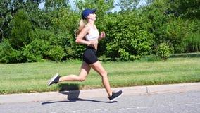 Den unga kvinnan joggar öva cardio genomkörare Den attraktiva sportiga kvinnan som in k?r, parkerar arkivfilmer