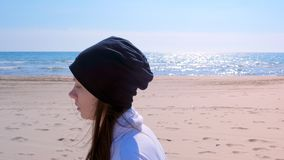 Den unga kvinnan joggar på jogger för stående för havssandstrand, körnings somsporten passade utomhus arkivfilmer