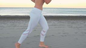 Den unga kvinnan joggar på sandstranden förbi havet på soluppgång i hösten, sikt för närbildbensida arkivfilmer