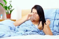 Den unga kvinnan känner sig törstig i morgonen Royaltyfri Foto