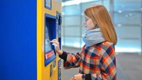 Den unga kvinnan köper en biljett i varuautomaten som väljer på pekskärmen stock video