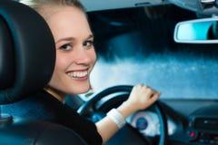 Den unga kvinnan kör bilen i wash posterar Arkivbild