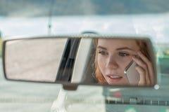 Den unga kvinnan kör en bil och samtal på telefonen royaltyfria foton