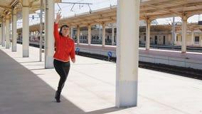 Den unga kvinnan kör längs plattformen som fångar upp med drevet stock video