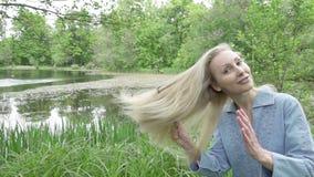 Den unga kvinnan kammar ett långt ganska hårhår mot bakgrunden av sjön långsam rörelse lager videofilmer