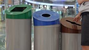 Den unga kvinnan kastar avfall i avfallfacket F?rlorad sortering och ?tervinning l?ngsam r?relse lager videofilmer