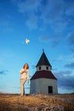Den unga kvinnan kastar upp hennes hatt vid solnedgång nära kyrkan arkivbild