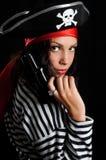 Den unga kvinnan klädde som en piratkopiera i en hol för svart hatt Royaltyfri Fotografi