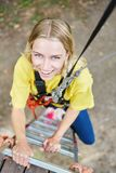 Den unga kvinnan klättrar upp en stege i den höga repkursen arkivbilder