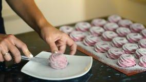 Den unga kvinnan klipper marshmallowen med kniven i kök av lägenheten inomhus stock video