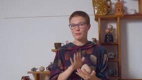 Den unga kvinnan knådar leran i hennes händer stock video