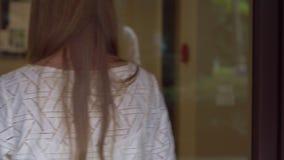 Den unga kvinnan kommer till hennes lägenhet och öppnar ett elektroniskt lås genom att använda ett nyckel- kort lager videofilmer