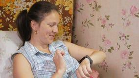Den unga kvinnan kontrollerar meddelandena på smartwatchen hemma på soffan lager videofilmer
