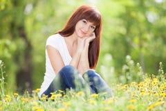 Den unga kvinnan kopplar av i parkera med blommor Skönhetnaturplats Arkivfoton