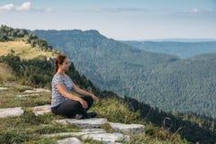 Den unga kvinnan kopplar av och mediterar bara överst av berget i den varma sommardagen, sund livsstil Arkivbilder