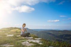 Den unga kvinnan kopplar av och mediterar bara överst av berget i den varma sommardagen, sund livsstil Arkivfoton