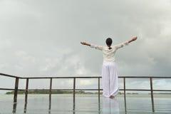 Den unga kvinnan kopplar av på molnig sommardag Fotografering för Bildbyråer