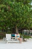 Den unga kvinnan kopplar av på stranden Arkivbilder