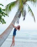 Den unga kvinnan kopplar av på stranden Royaltyfria Bilder