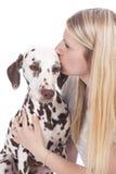 Den unga kvinnan kysser den dalmatian hunden Fotografering för Bildbyråer