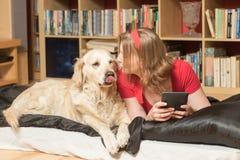 Den unga kvinnan kysser hennes hund inomhus arkivfoto