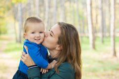 Den unga kvinnan kysser hennes lilla son royaltyfri bild
