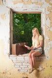 Den unga kvinnan läser en bok Arkivbild