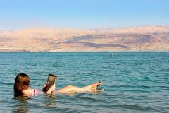 Den unga kvinnan läser en bok som svävar i det döda havet i Israel Royaltyfri Bild