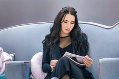 Den unga kvinnan läser en tidskrift, medan vänta i en friseringsalong Royaltyfri Fotografi