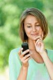 Den unga kvinnan läser sms på mobil Arkivfoton