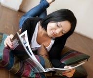 Den unga kvinnan läser tidskriften royaltyfri bild