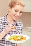 Den unga kvinnan lagar mat sallad Arkivfoton