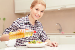 Den unga kvinnan lagar mat sallad Royaltyfria Bilder